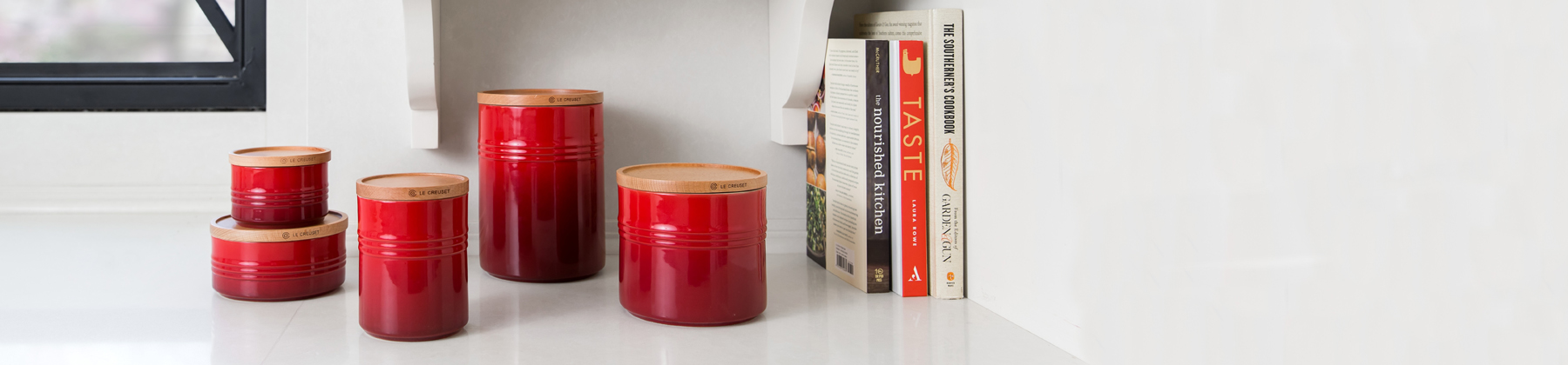 Countertop showcasing Le Creuset red canisters, books, and candles.