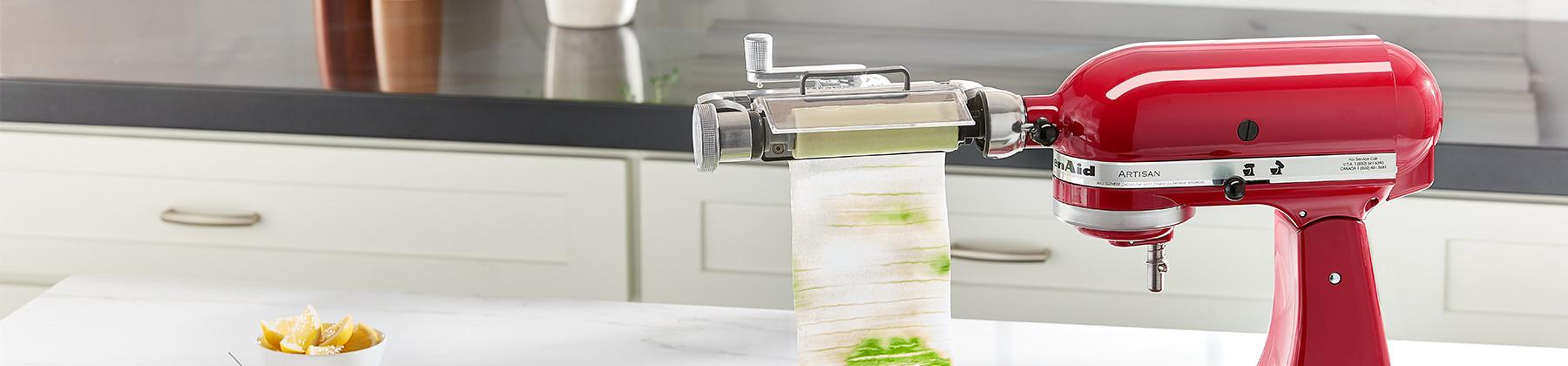 Photo of a KitchenAid Sheet Cutter Attachment cutting cucumber on a KitchenAid mixer.